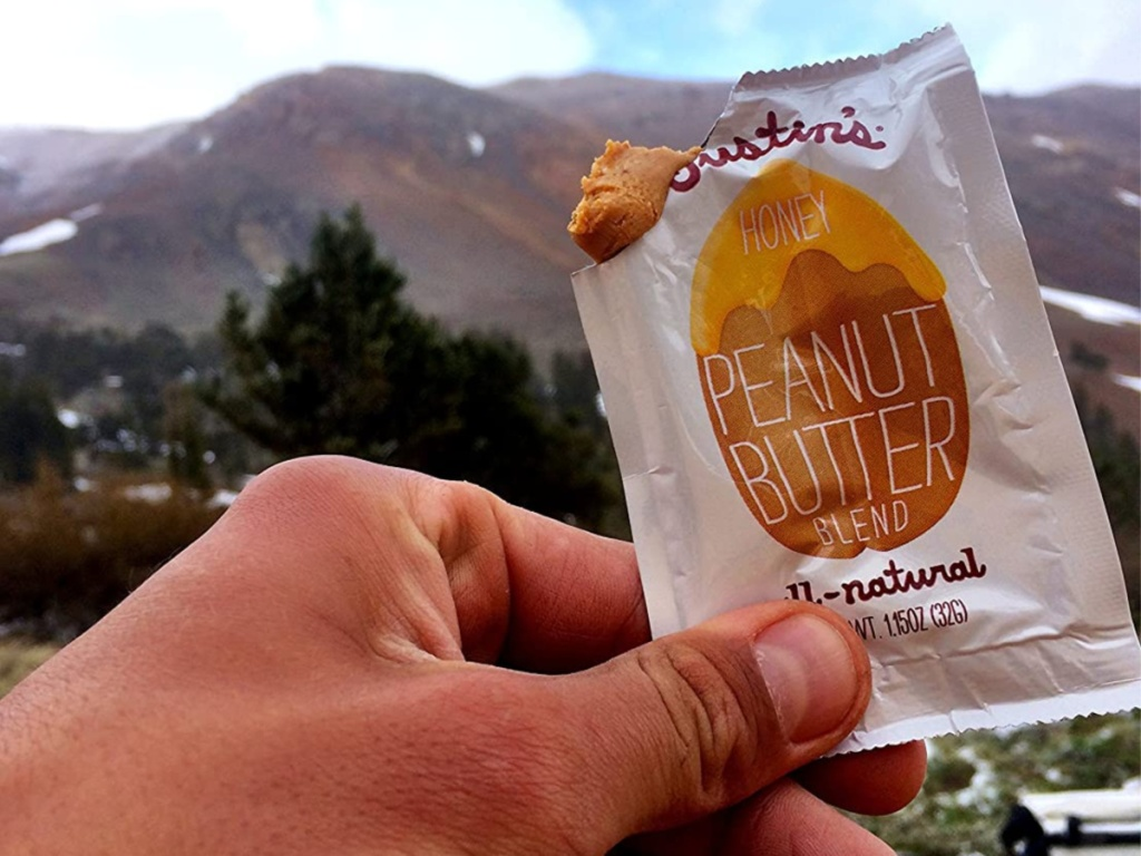 hand holding honey peanut butter squeeze pack with mountains in background