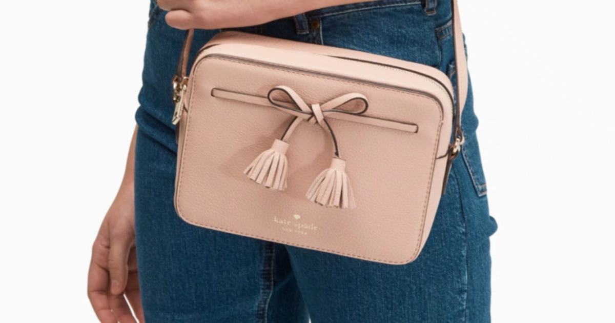 Small square, pink camera bag. Held by a lady wearing jeans