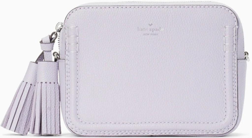 Lavender colored crossbody handbag with Kate Spade logo and matching tassel