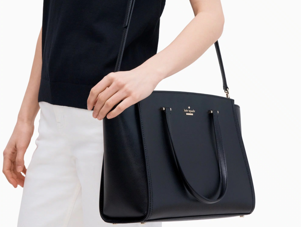 woman in black shirt and white pants carrying black kate spade tote abg