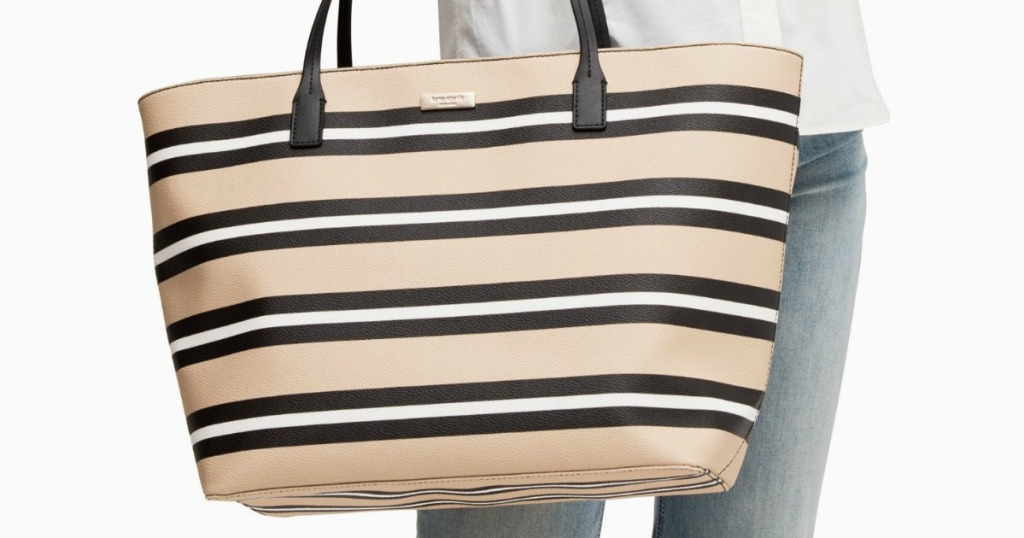 woman carrying a black and tan tote