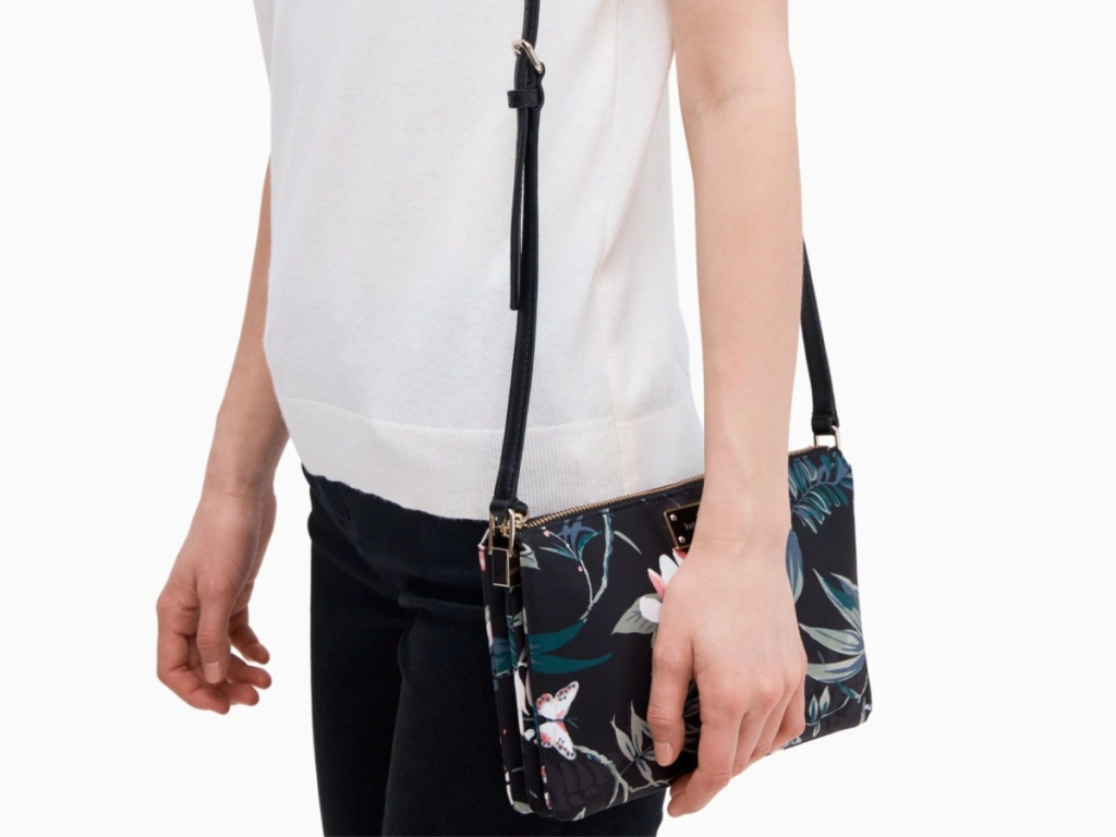 woman in white shirt and black jeans carrying flower print kate spade bag
