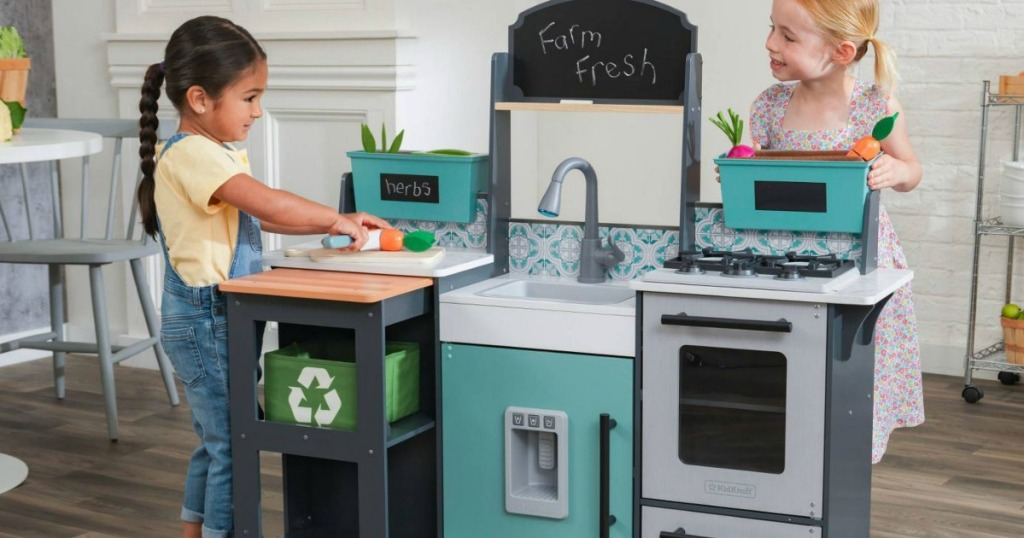 girls playing with a kids kitchen