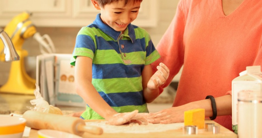 Kid cooking in kitchen with parent