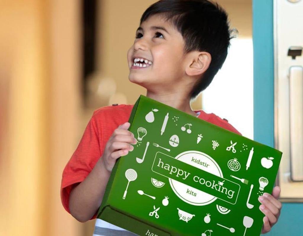 boy holding green kidstir cooking kit