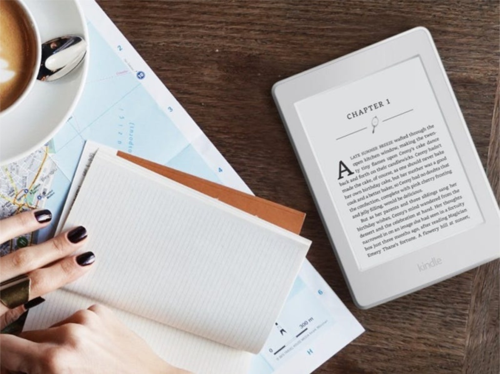 eBook reader, coffee, paper, and notebook on wooden table