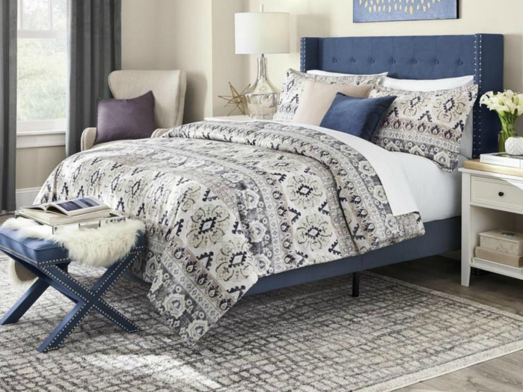 Large king sized bed with blue tuft headboard in coordinating bedroom
