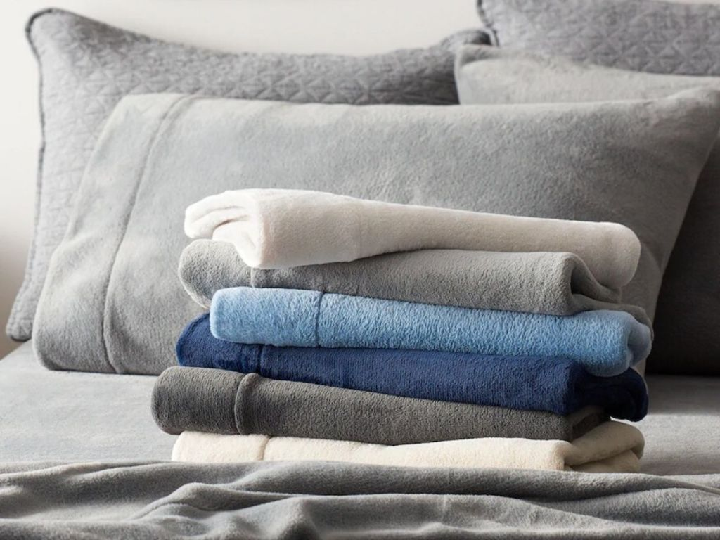super soft sherpa sheets folded on a bed with sherpa pillows in the background