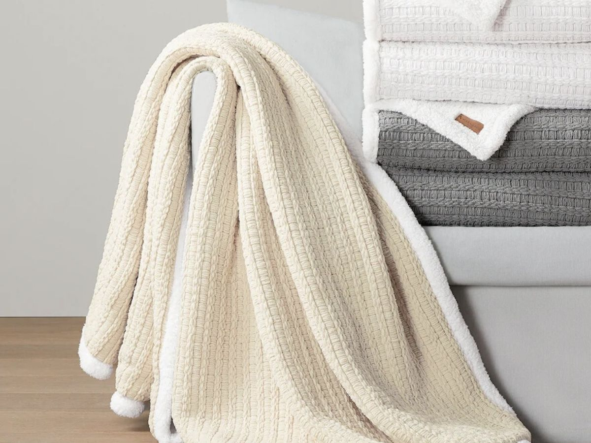 plush blanket draped over end of couch next to stack of similar blankets in different colors