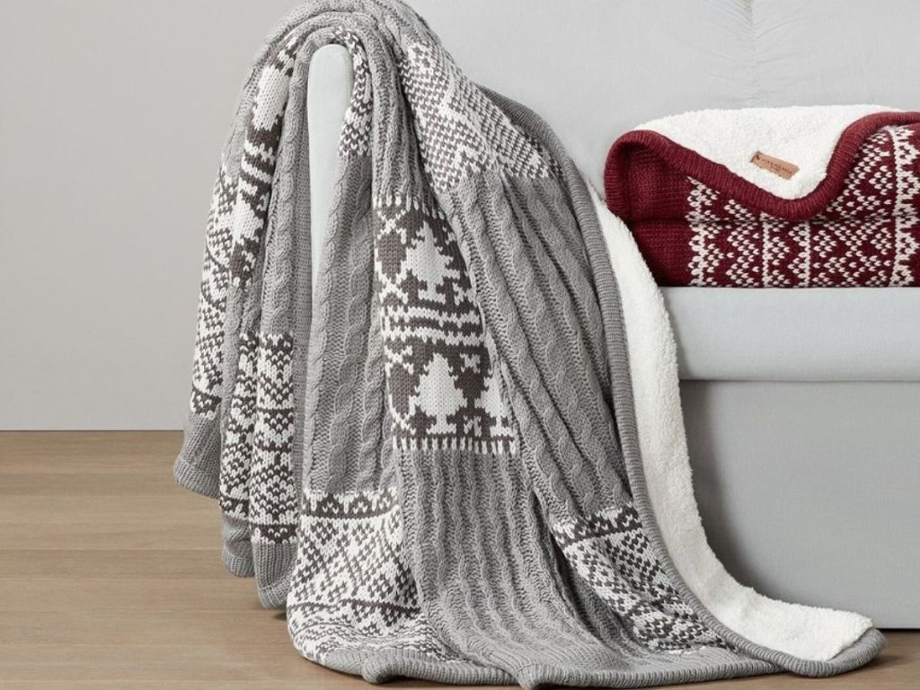 Sherpa blanket draped over arm of couch next to identical blanket folded up