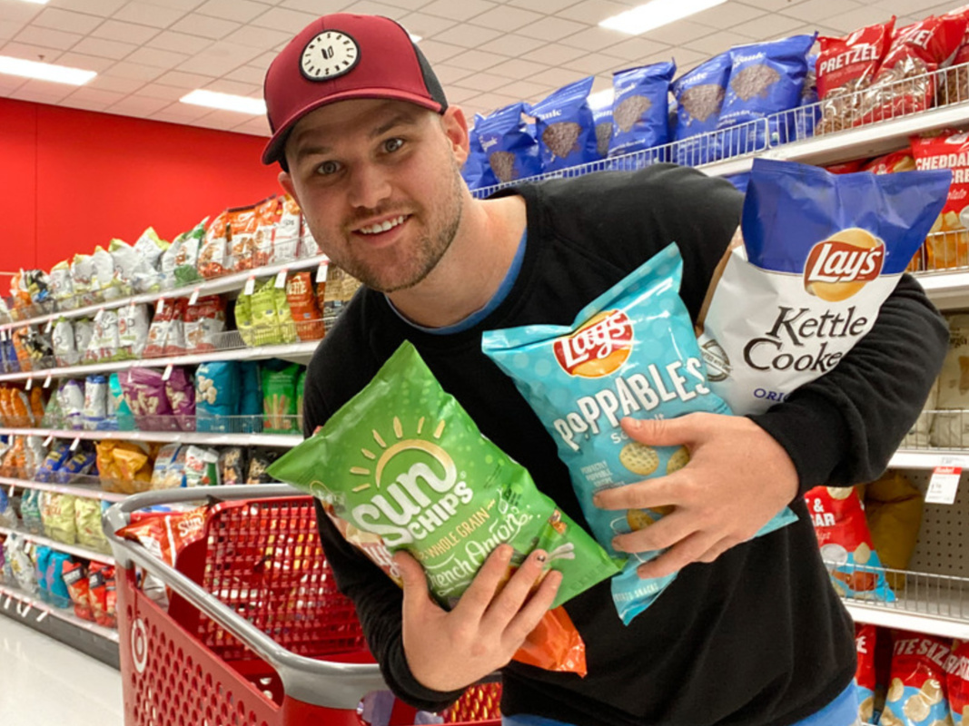 Man holding bags of chips in store aisle