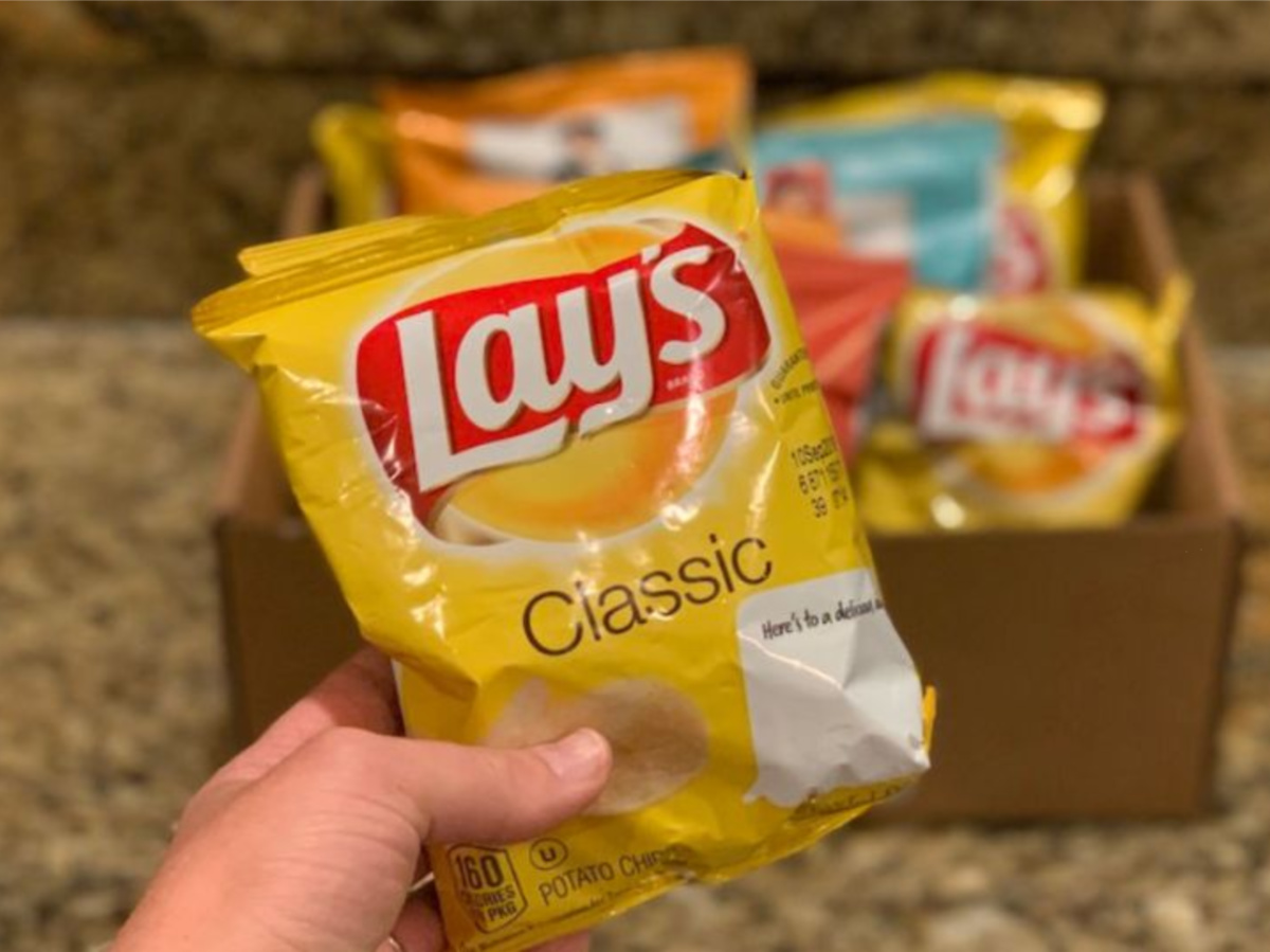 hand holding small bag of chips in front of box of chip bags