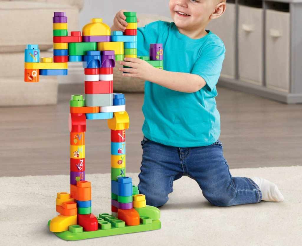 little boy playing with a large set of blocks on living room floor