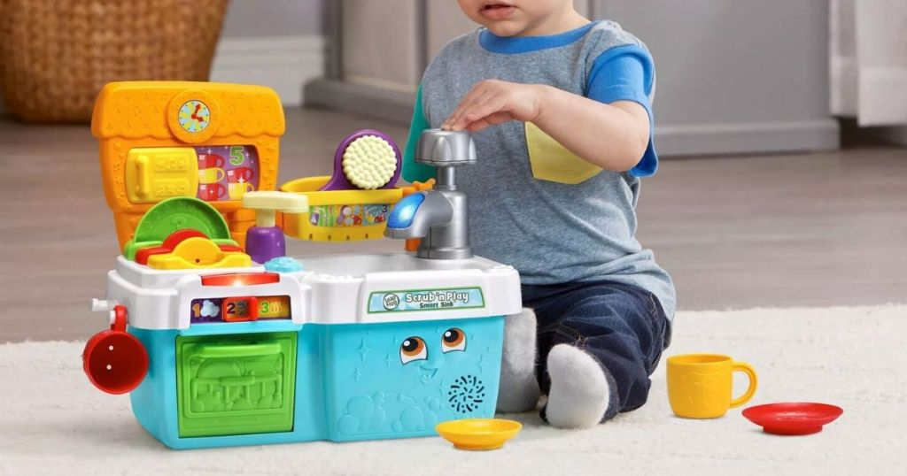 little boy playing with toy sink set on carpet