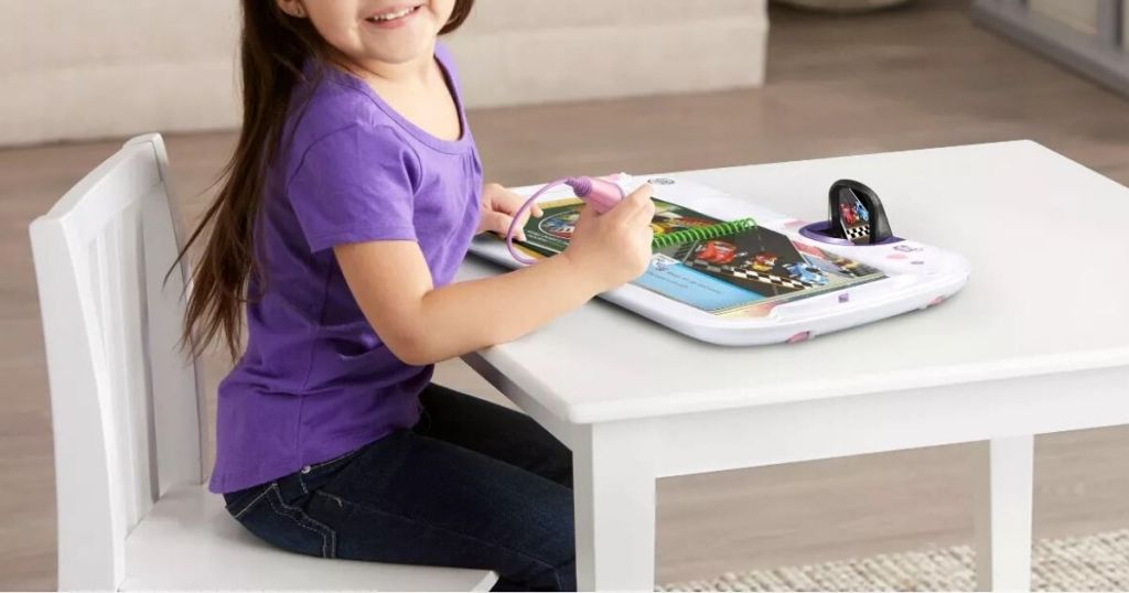 little girl sitting at table using leapfrog interactive book toy