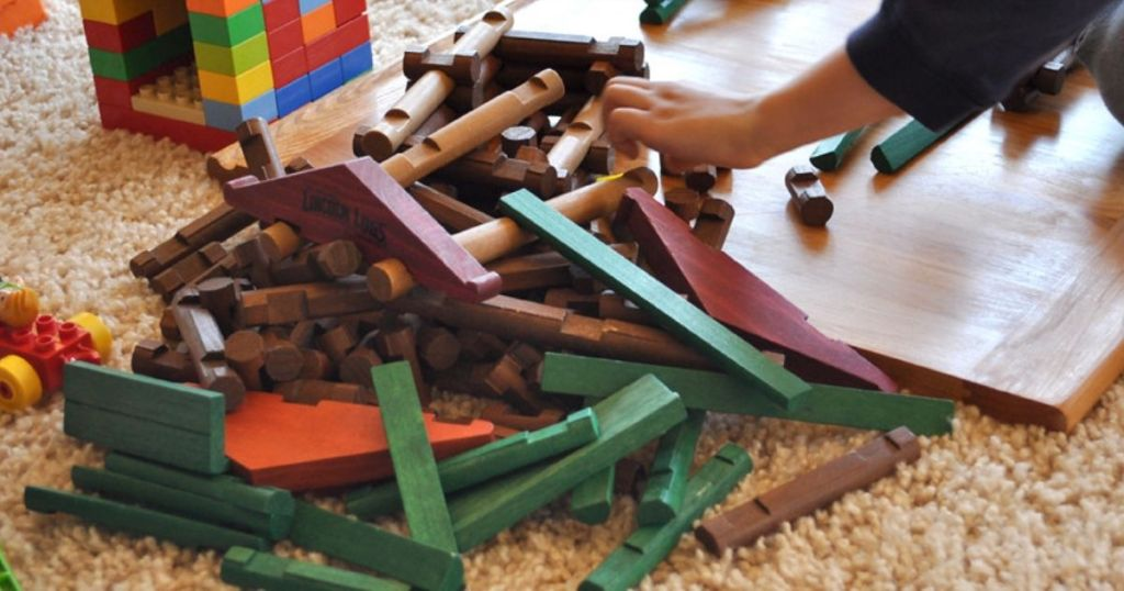 Child grabbing Lincoln Logs from pile on the floor
