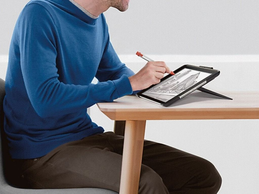 man working on ipad with digital pen sitting at table