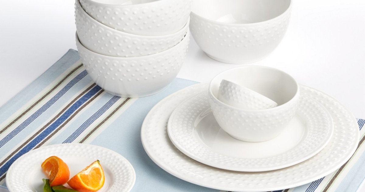 white embossed plates and bowls on blue table cloth on table with plate of orange slices