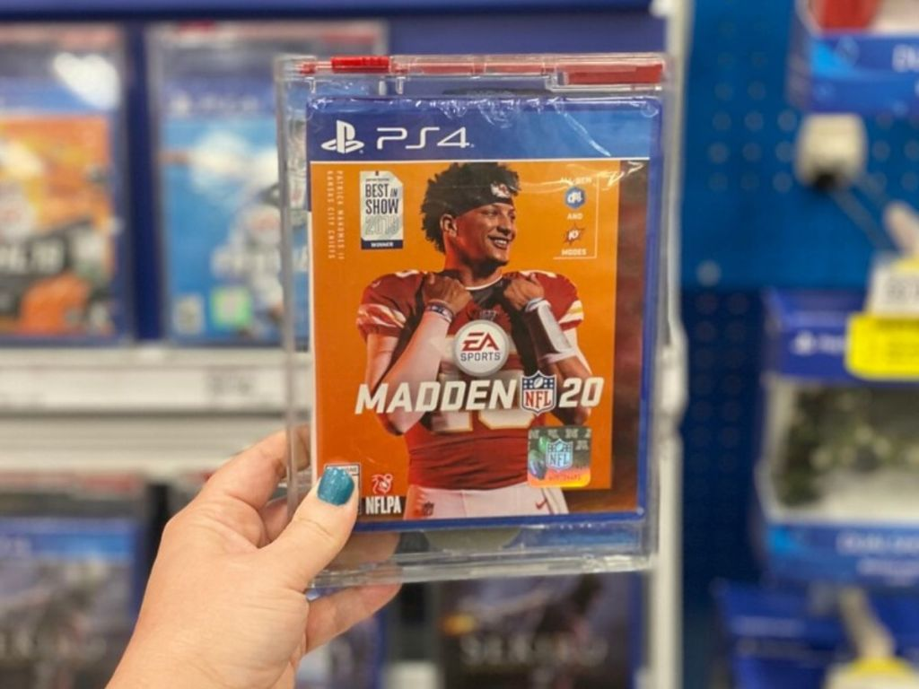 womans hand holding up football video game in case at store
