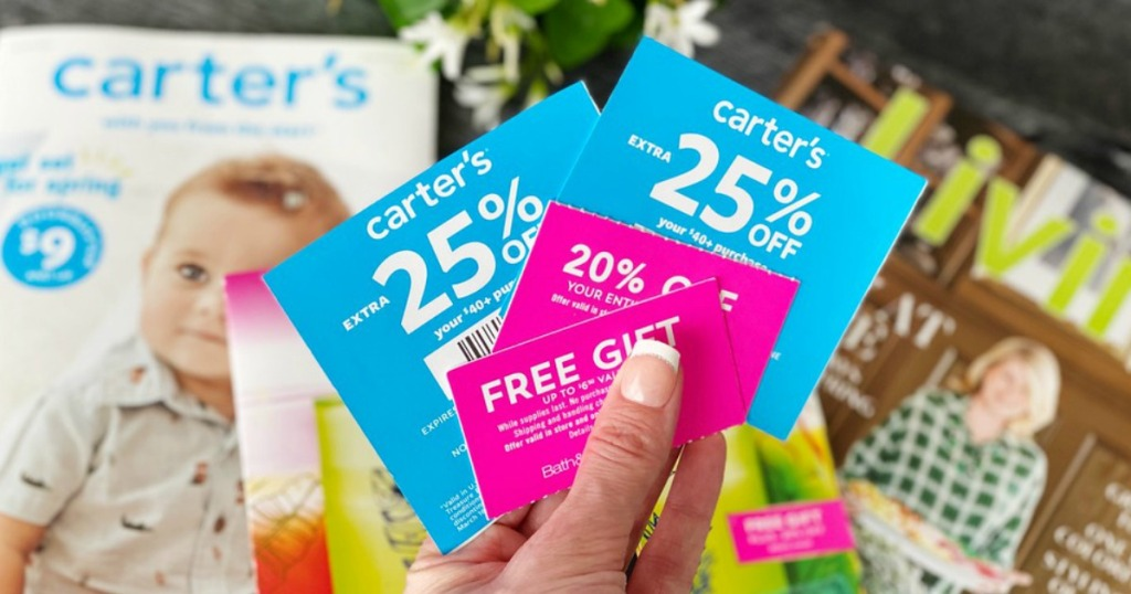 lady holding various coupons for Carter's, BBW and more