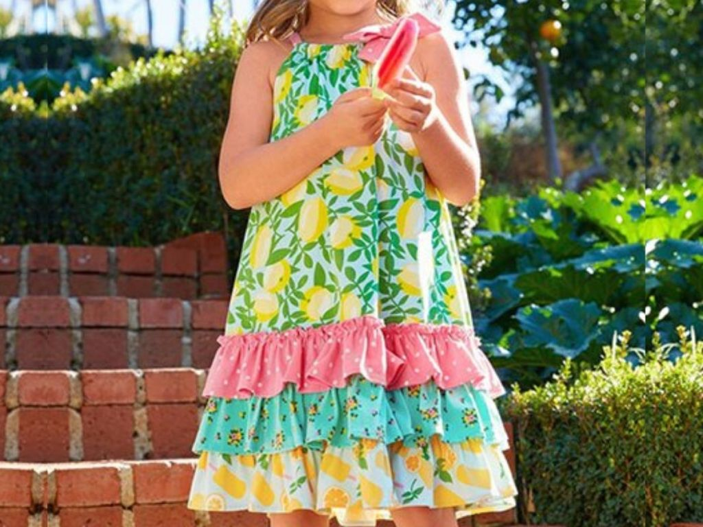 little girl wearing frilled summer dress, eating a popsicle on front of brick stairs