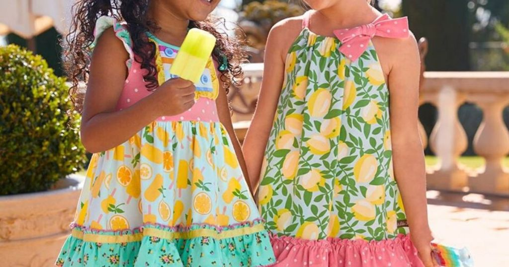 two girls wearing colorful summer dresses eating popsicle