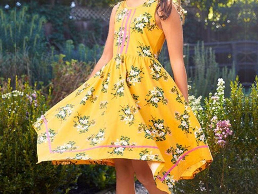 girl twirling in hankerchief dress outside