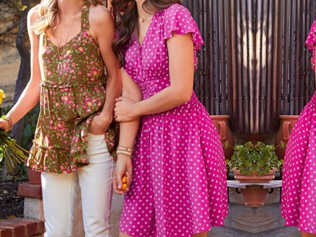 two women standing with arms interlocked wearing summer style clothing outside