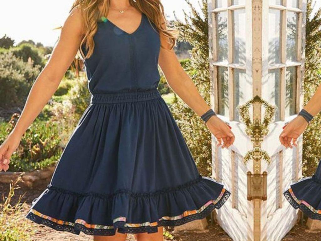 woman wearing swing style summer dress outside near door