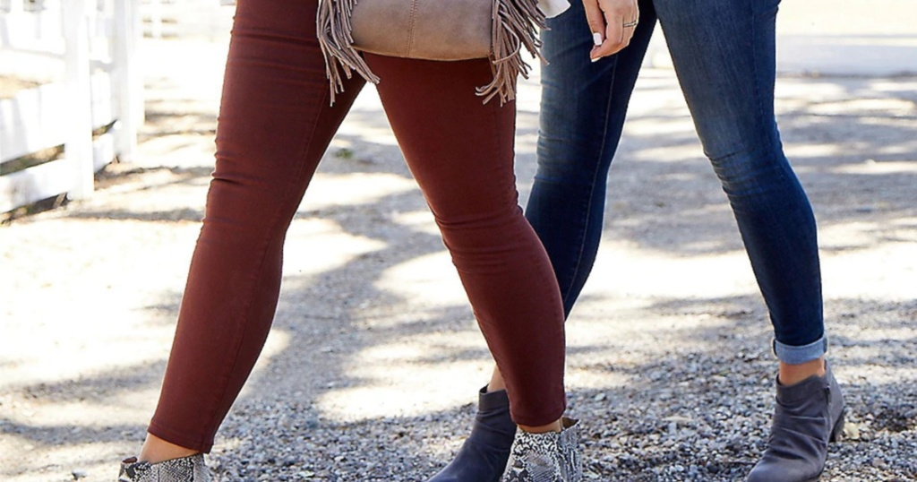 two women walking outside in booties and jeans