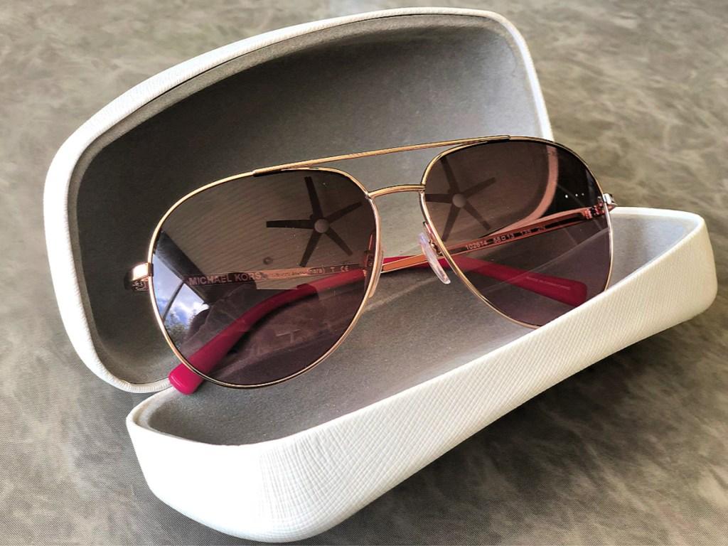 Michael Kors Rodinara Aviator Sunglasses in case on table