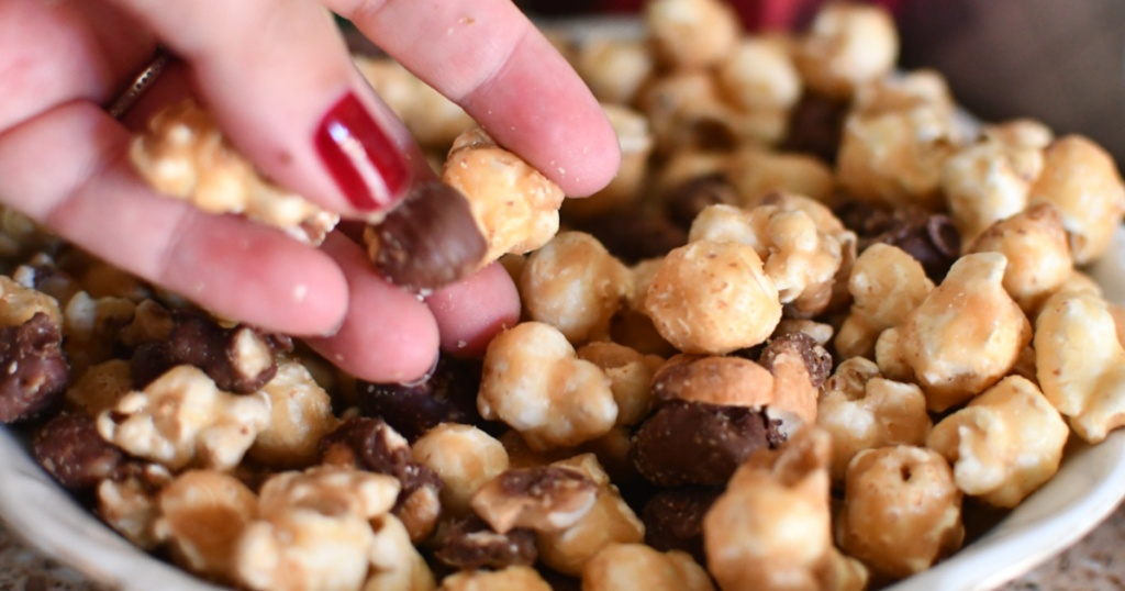 hand holding chocolate covered popcorn from bowl