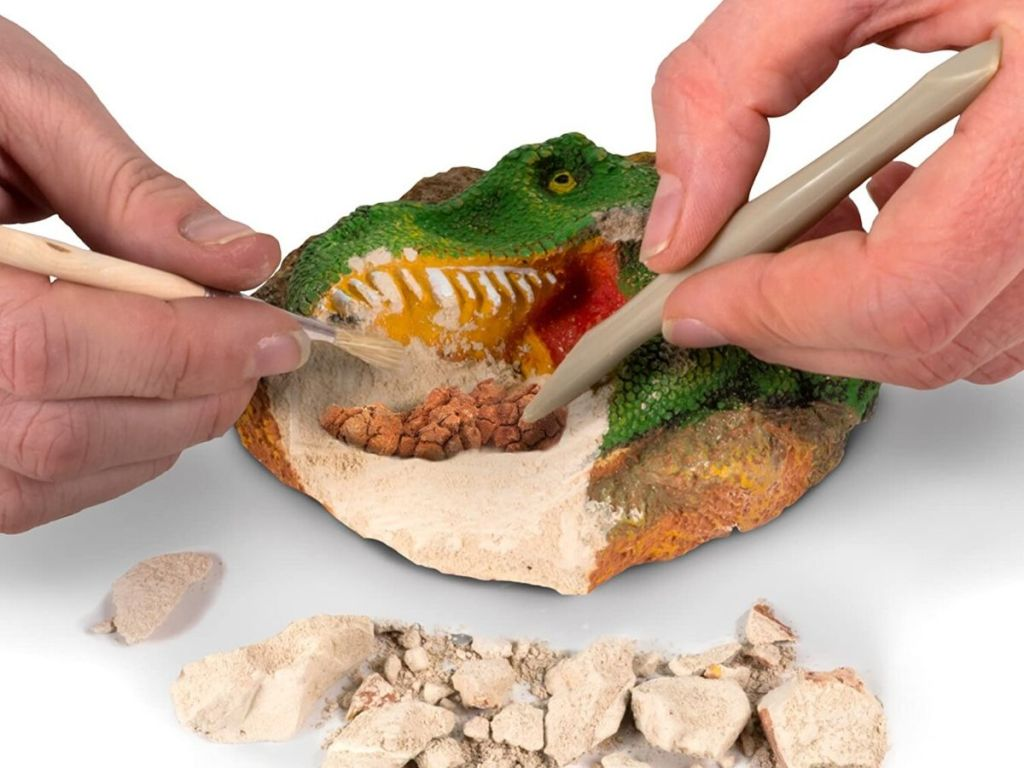 hands chiseling dinosaur excavation kit toy