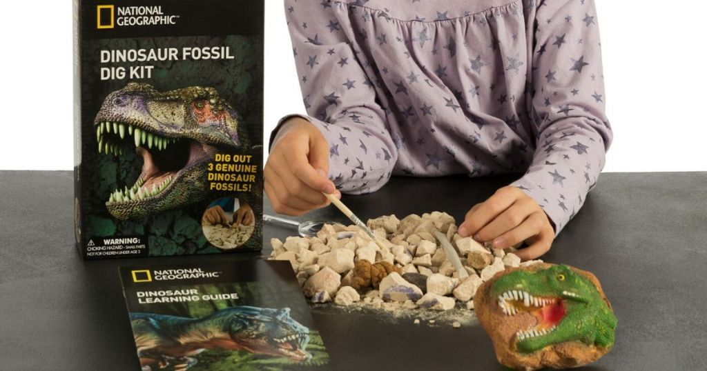 girls hand demonstrating dinosaur fossil dig kit next to toy's box