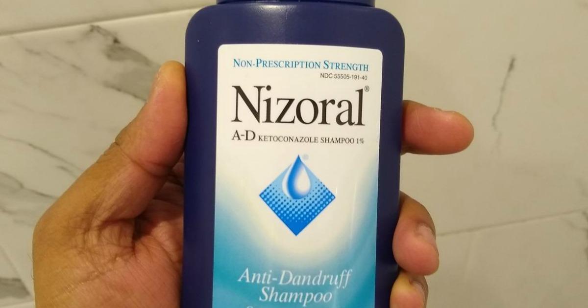 Hand holding Nizoral Shampoo
