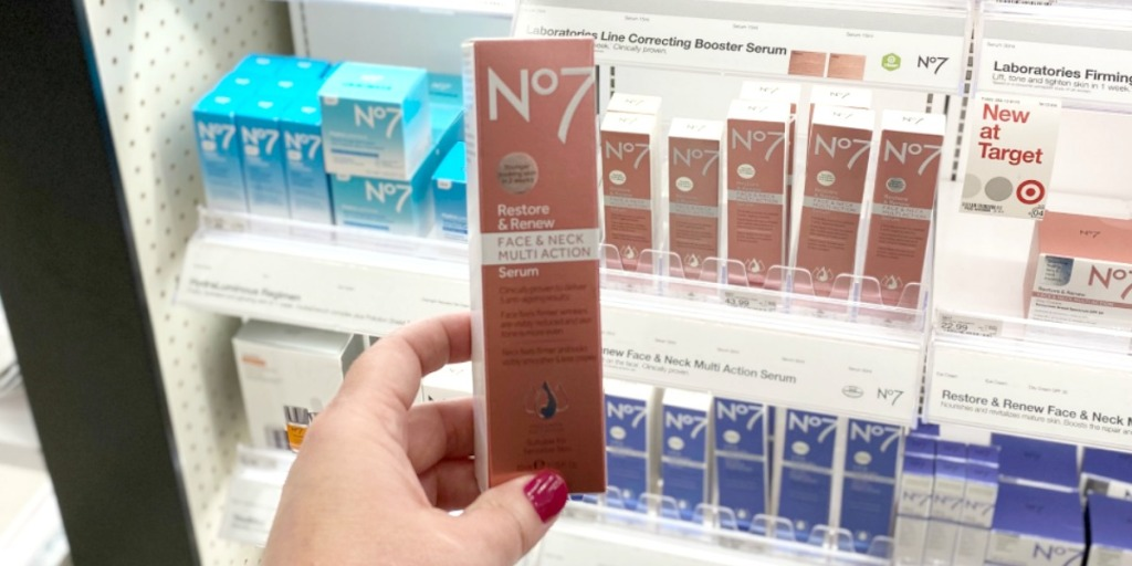 Woman's hand holding up a box of neck serum