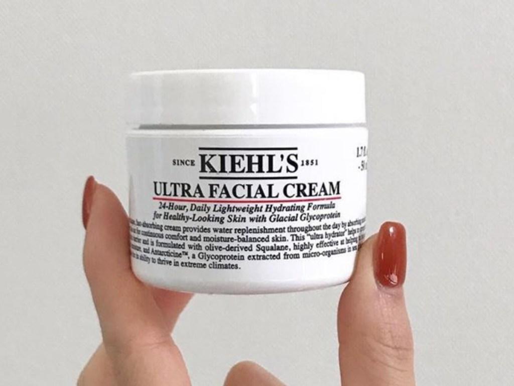 Woman's hand holding kiehl's ultra facial cream