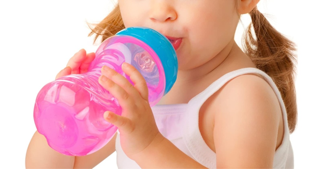 little girl holding pink sip cup