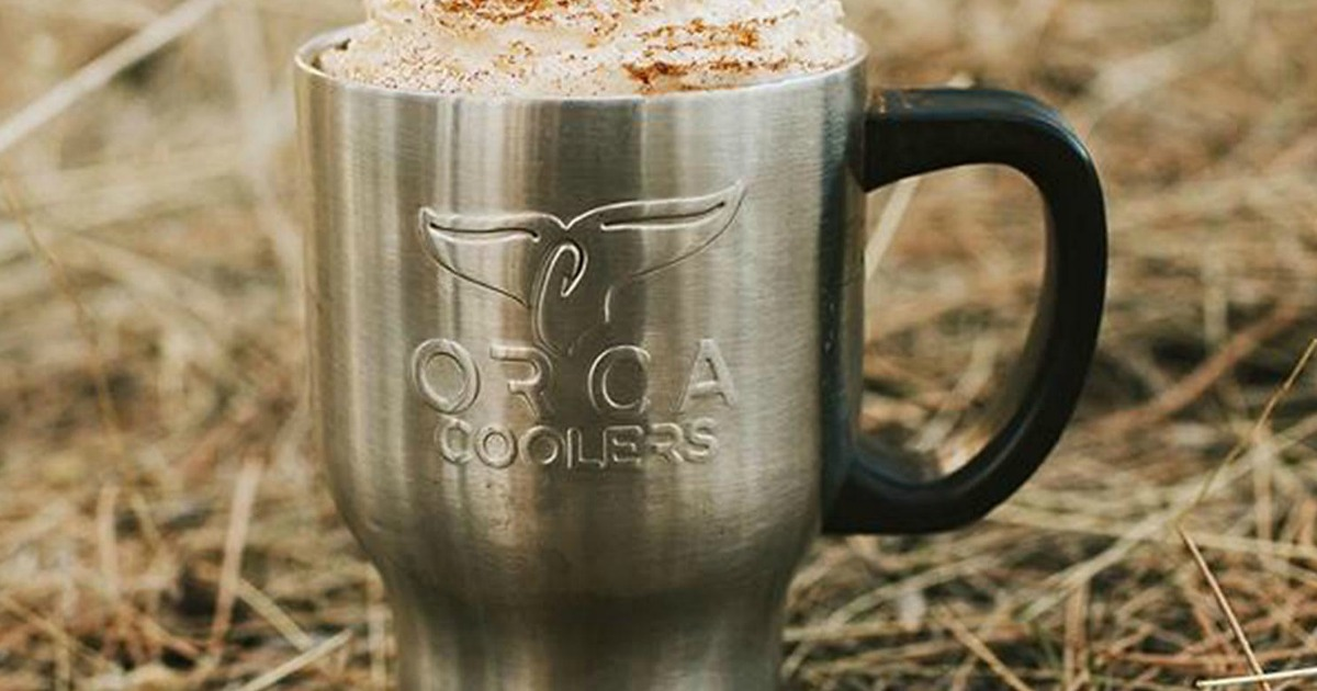 Orca Coolers mug with foam sitting on hay