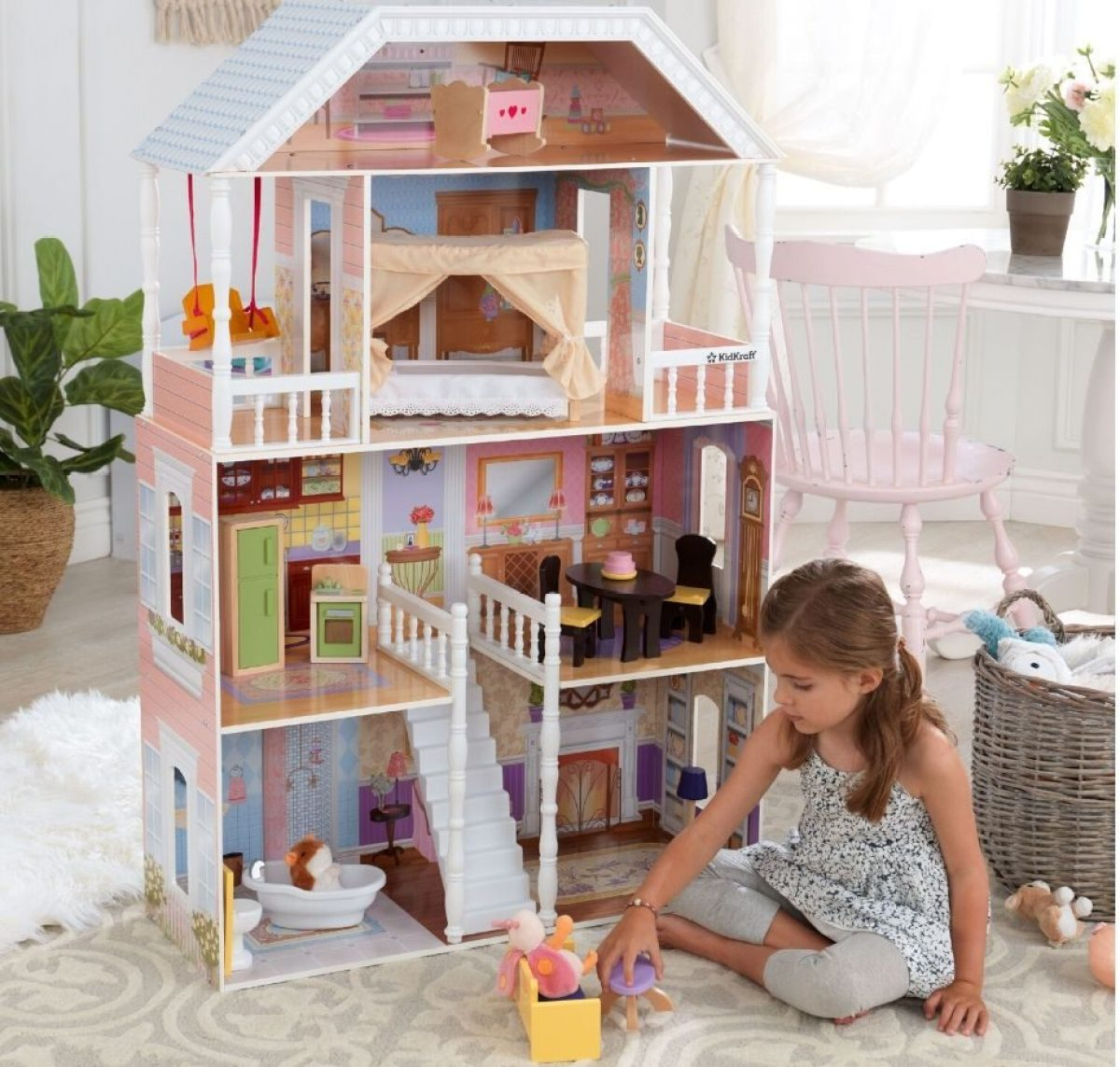 Little girl playing on floor with giant dollhouse