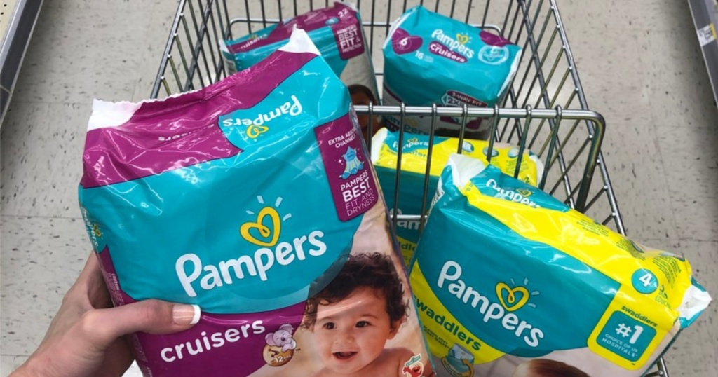 woman holding diaper package over cart of diapers in store