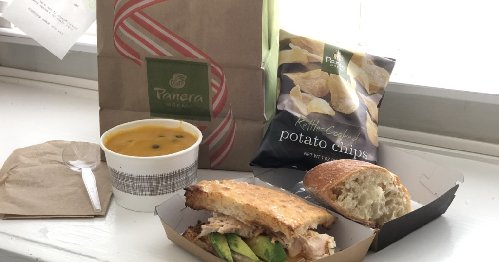 panera sandwich, chips, and soup in to go container with bag on counter