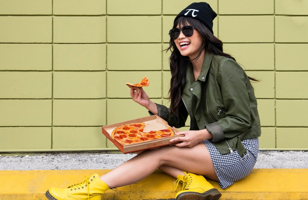woman in Pi hat eating pizza
