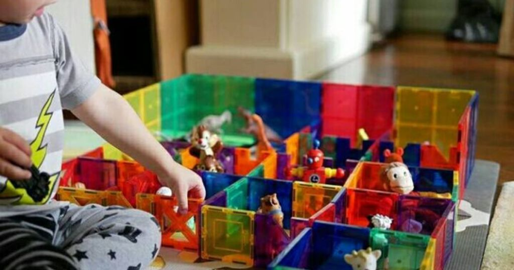 toddler playing with plastic building tiles making fences for plastic animals