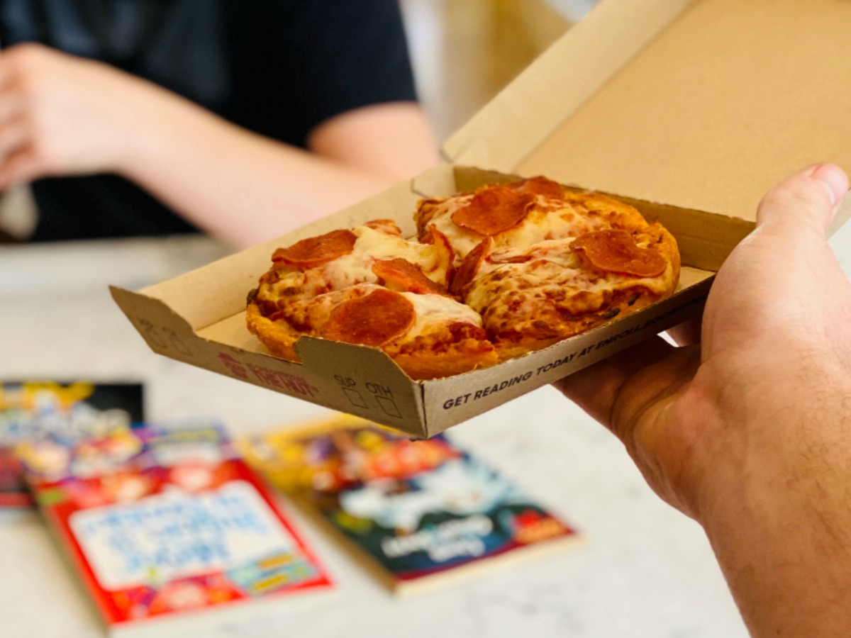 hand holding a personal pepperoni pizza in a box