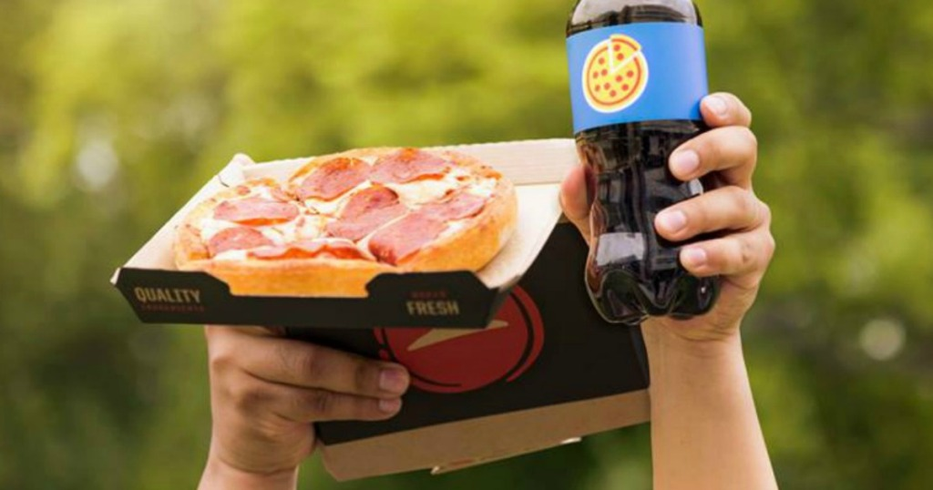 Kid holding up Pizza Hut Personal Pizza and soda