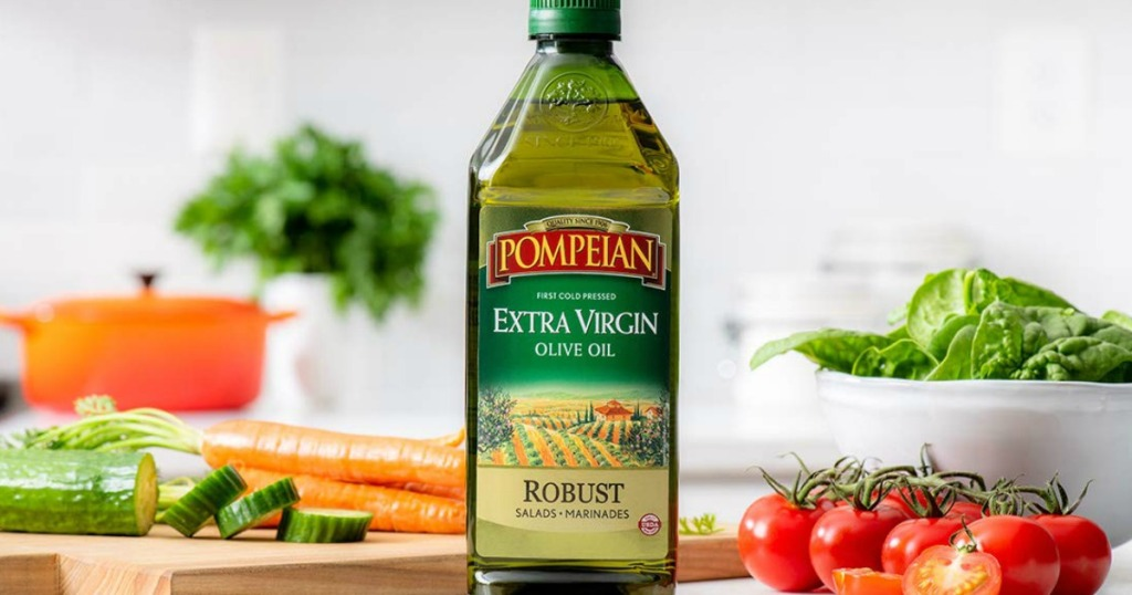 Pompeian Robust Extra Virgin Olive Oil on counter with vegetables in the background