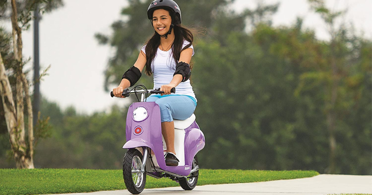 girl riding purple scooter outdoors