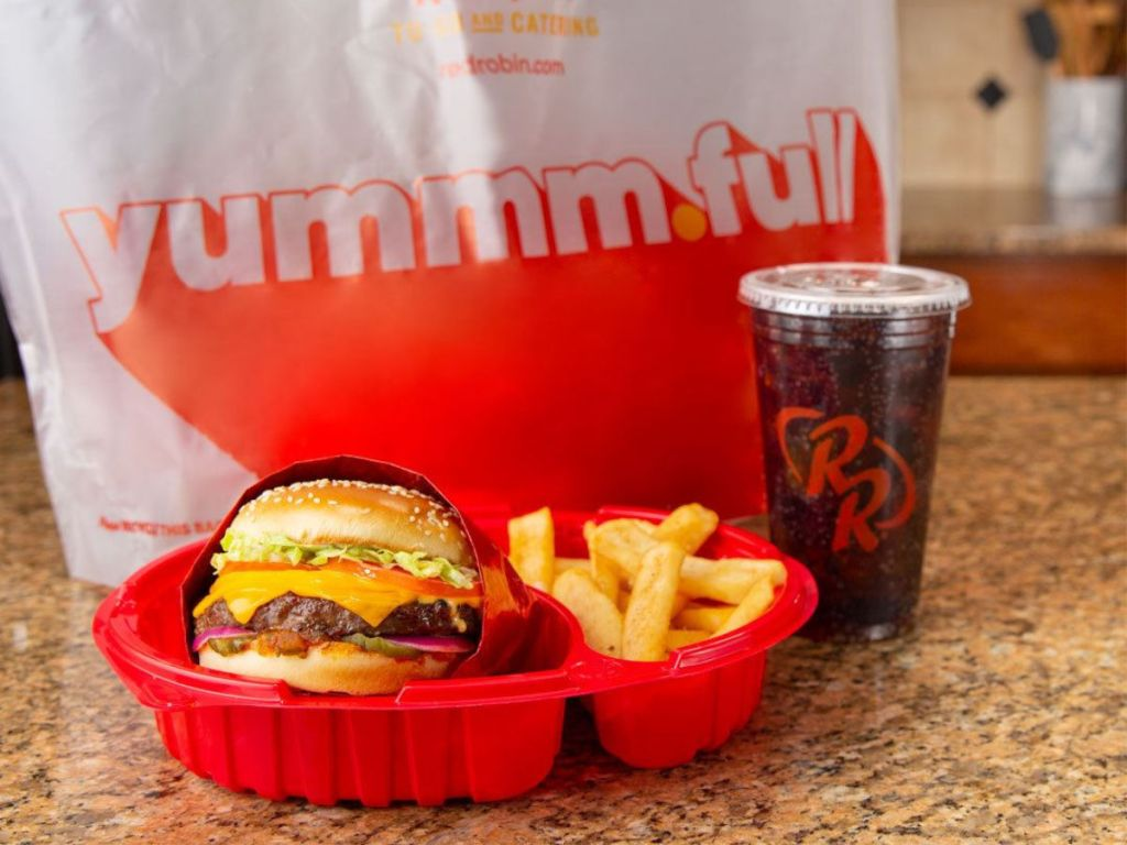 Red Robin Meal with burger, fries, and soda with to go bag in the background