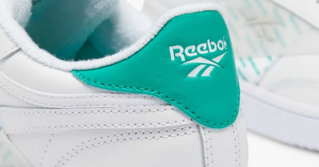pair of white shoes with teal logo on heel